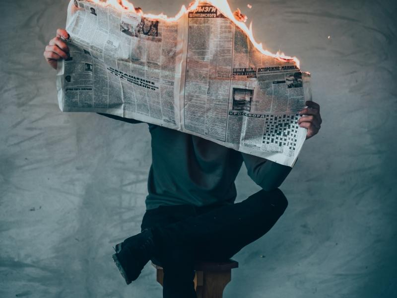 newspaper on fire